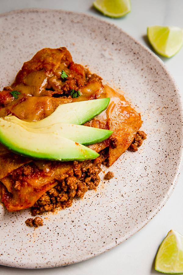 Serving of enchilada skillet served on plate with avocado slices