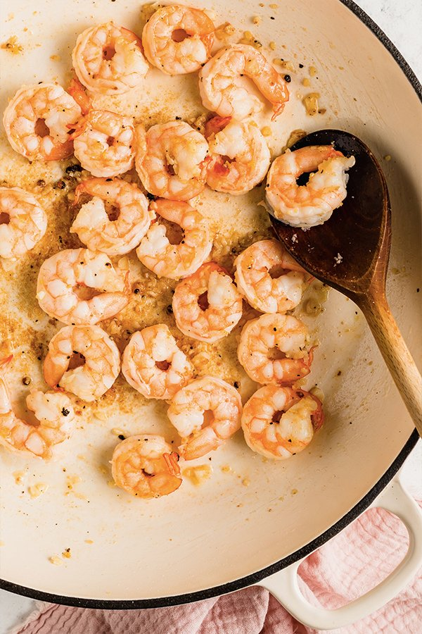 Shrimp cooked in pan with wooden spoon