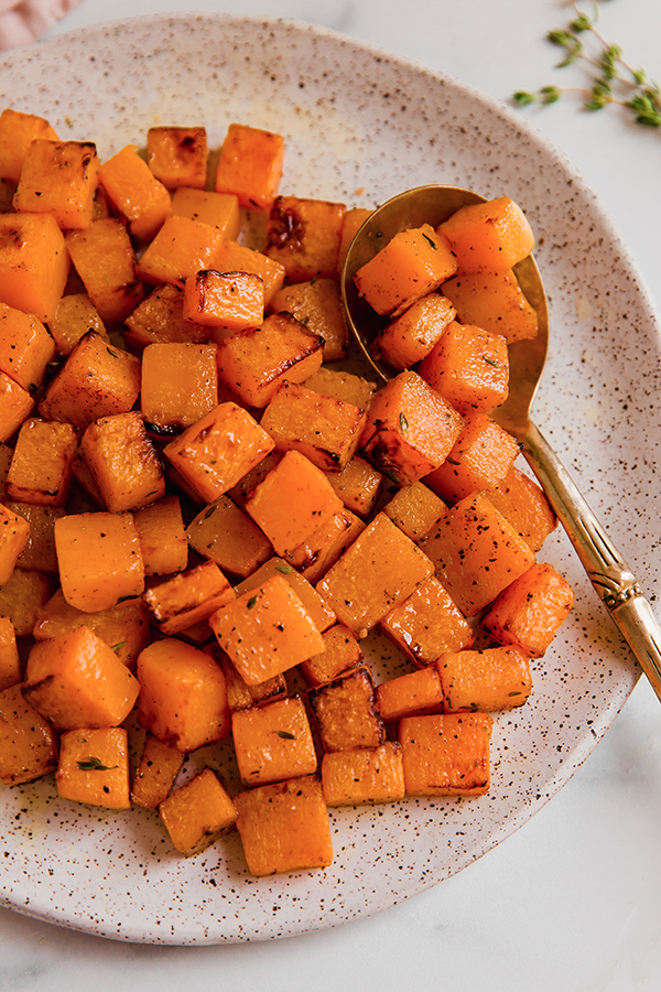 squash cubes of a plate with a spoon