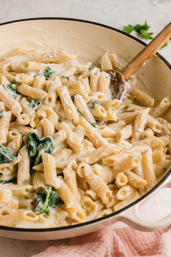 A pot of Easy Penne Alfredo with a wooden spoon in it.