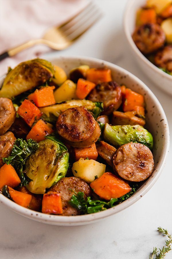 A white bowl filled with apple chicken sausage and harvest vegetable skillet.